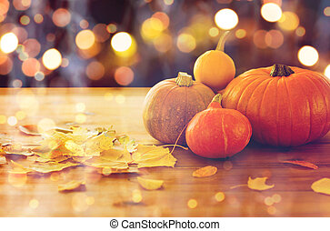 close up of halloween pumpkins on wooden table - food,...