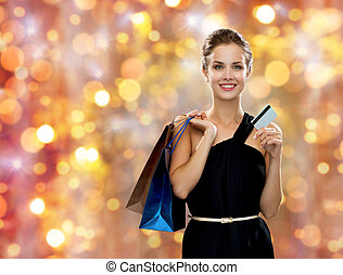 smiling woman with shopping bags and credit card - sale,...