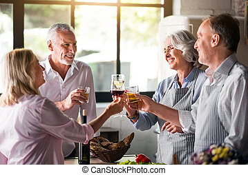 Family cheering with whiskey and wine in kitchen - Together...