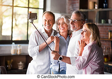 Two elderly couples taking photo in the kitchen - Happy...