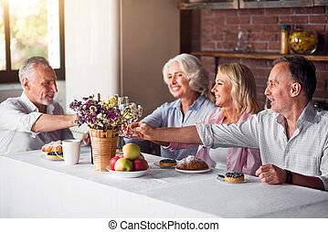 Joyful family gathering at kitchen table and drinking wine -...