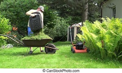 worker guy shake pour grass from lawn mower bag into...