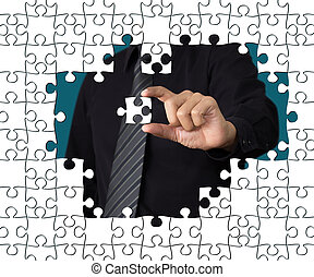 Business concept: Hand holding one pieces of a puzzle