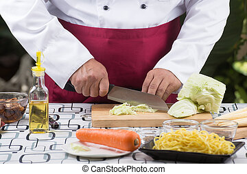 Chef sliing cabbage on wooden broad - Chef slicing cabbage...