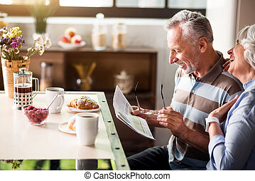 Elderly caucasian male and female reading the newspaper -...
