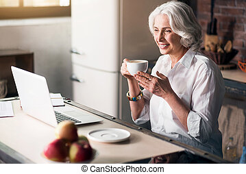 Erderly woman using computer while enjoying her coffee -...