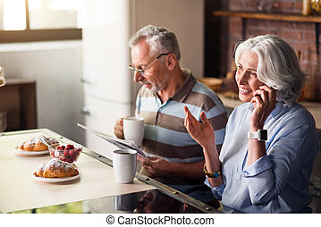 Attractive male and female pensioners having breakfast in...