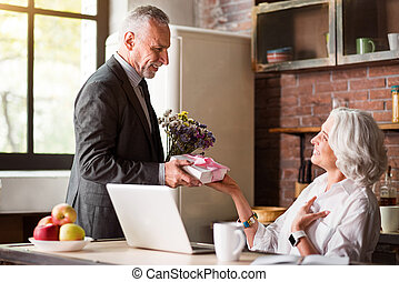 Elderly man giving present and flowers to his happy wife -...