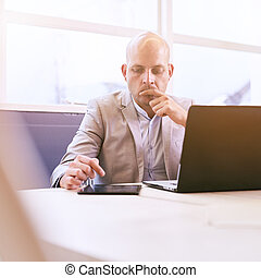 Professional business man working on his portable tablet and...