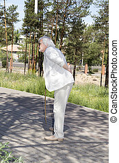 an elderly man with back pain - An elderly man goes down the...