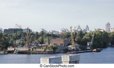 Industrial cityscape with crane unloading cargo against the...