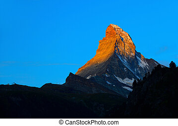 Matterhorn in early morning with alpenglow and blue sky in...
