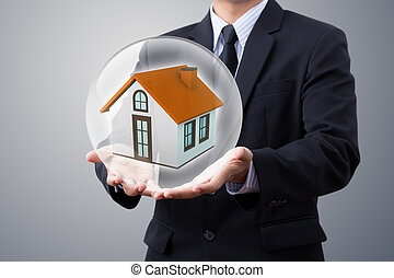 hands saving small house in crystal ball (insurance, home, house)