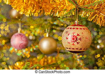 Decoration bauble on decorated Christmas tree background -...