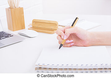 Girl's hand writing in notepad - Side view of girl's hands...
