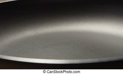 SLOW: Water falls on a black pan