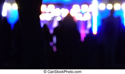Blurred people going to night show. Bright stage lighting....