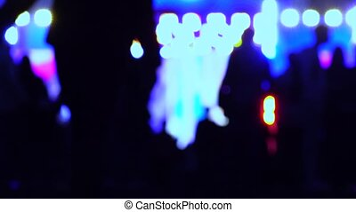 Defocused people silhouettes heading for night show. 4K background bokeh shot