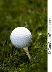 Golf Ball and Tee - A white golf ball set up on the tee in...