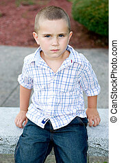 Little Boy By Himself - A little boy with a serious or bored...