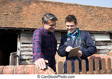 Farmer And Vet Looking At Digital Tablet Together
