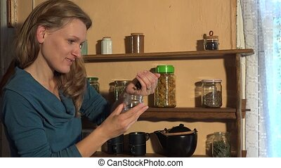 Country woman pour clove spices into small glass jar. 4K -...