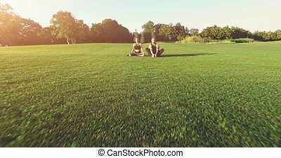 Yoga on green grass outdoor. 4k, 25fps - 4K shooting: Aerial...
