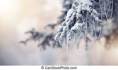 Snow-covered fir-tree branch with Christmas-tree decoration...