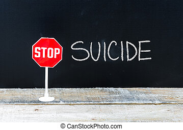 STOP SUICIDE message written on chalkboard - Mini STOP sign...