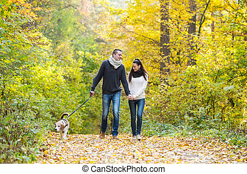 Young couple with dog on a walk in autumn forest - Beautiful...