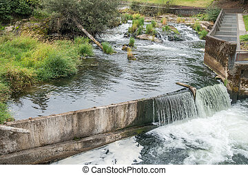 Manmade Waterfall 3 - Water flows over a wall on the...