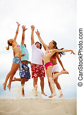 High jump - Photo of five friends in high jump over sandy...