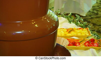 Chocolate flow. Fountain cascades hot chocolate. - Chocolate...