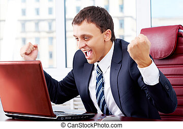 Triumph - Portrait of happy businessman looking at laptop...