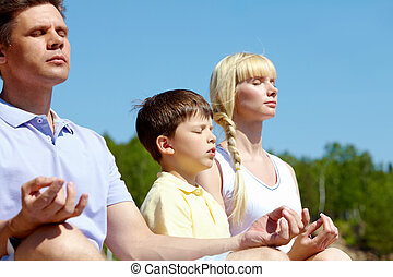 Harmony - Photo of three family members meditating on summer...