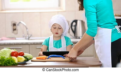 little girl with a tablet in the kitchen eating carrot