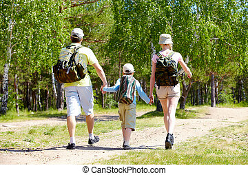 In the forest - Rear view of dynamic family members going...