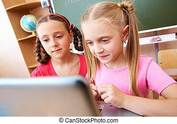 Computer studies - Portrait of two schoolgirls looking at...