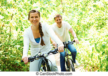 Healthy life - Photo of happy woman riding bicycle outdoors...