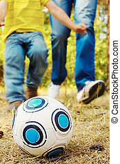 Outdoor game - Image of ball on ground in park with child...