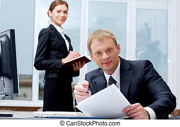 Boss at workplace - Portrait of confident boss holding...