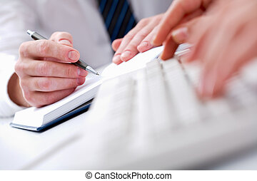 Planning - Close-up of male hands writing in notepad with...