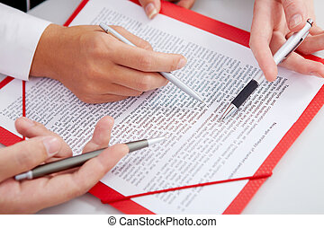 Reading paper - Close-up of business partners hands over...