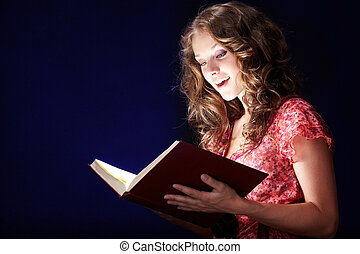 Reading magic book - Image of pretty girl looking into open...