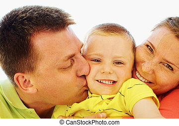 Devotion - Portrait of happy kid being kissed by his parents