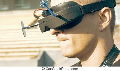 Man watching flight of FPV drone using VR glasses - Back...