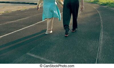 Senior couple walking along the running track