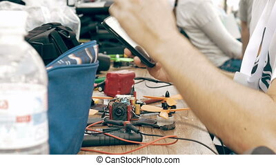 Man using smartphone while assembling FPV drone process,...