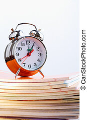Clock and copybooks - Stack of copybooks with alarm clock on...
