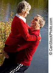 Carefree couple - Image of senior man holding his wife while...